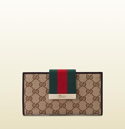 Gucci continental wallet with engraved gucci script logo.